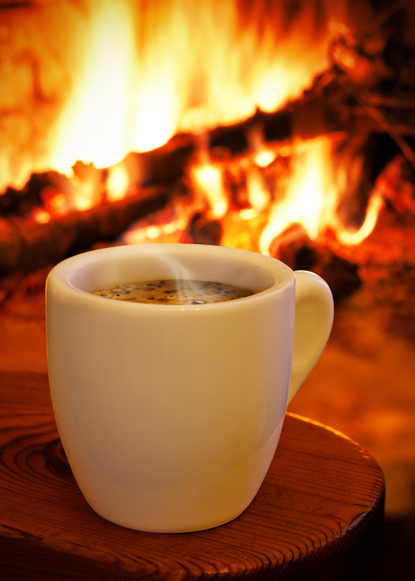 A cup of hot coffee in front of the fireplace