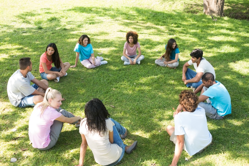 Group of multiethnic friends sitting in a circle at park