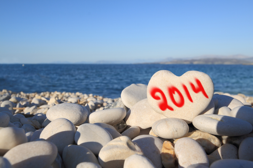 2014  new year written on heart shaped stone on the beach with spray brush